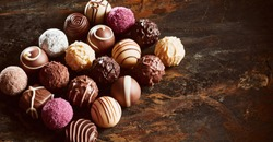 Luxury handmade chocolate praline still life arranged in a neat rectangle on rustic or vintage wood with copy space in banner format