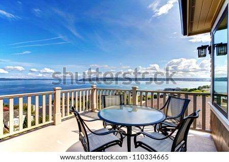 Luxury home balcony deck with water view and table with house.