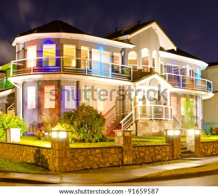 Luxury home exterior in the night time illuminated with lights