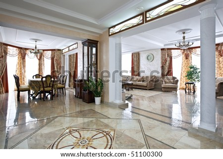 Luxury home interior with lobby, living room and table for dinner in daylight