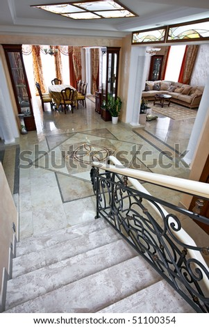Luxury home interior with staircase, lobby, living room and table for dinner in daylight