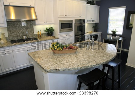 Luxury home kitchen with a hardwood floor and granite island.