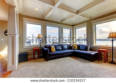 Luxury home living room with many windows and blue sofa.