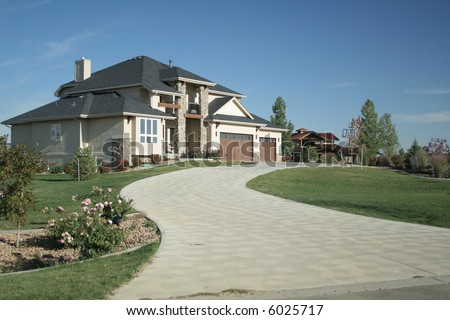 Luxury home with large driveway and landscaping