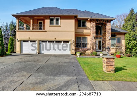 Luxury home with large grass yard and garage.