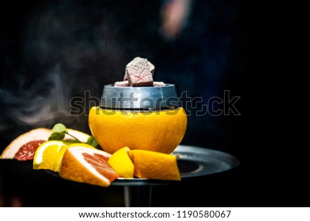 Luxury hookah with orange. Exotic bowl with fruit. Hookah lounge. Fruits and coals.  Glamours relax. Narghile and water pipe