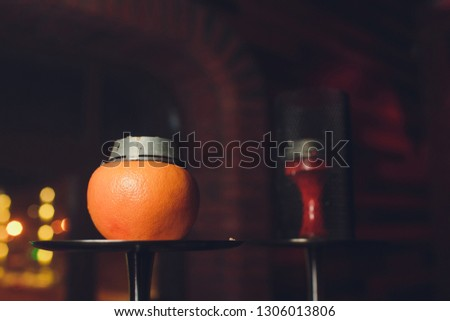 Luxury hookah with orange. Exotic bowl with fruit. Hookah lounge. Fruits and coals. Glamours relax. Narghile and water pipe.