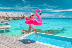 Luxury hotel beach vacation ocean overwater bungalows suite resort. Happy woman tourist jumping of joy in funny pool toy flamingo float excited to be in Bora Bora, French Polynesia.
