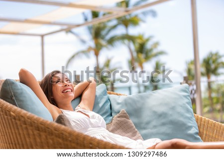 Luxury hotel home living woman relax enjoying sofa furniture of outdoor patio. Beautiful young multiracial Asian girl relaxing day dreaming for rich early retirement in getaway tropical house.
