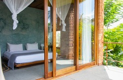 Luxury hotel room with mosquito net and open terrace. Comfortable interior of tropical hotel. Cozy and elegant bedroom design. Summer travel in tropics. Tourist resort. Bed with baldachin. Modern home