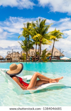 Luxury hotel swimming pool woman relaxing in lounging chair enjoying summer vacation. Tourist with hat and red swimsuit in water lounger.