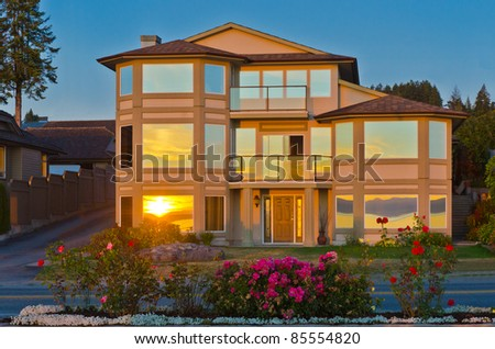 Luxury house at dusk with gorgeous reflections in windows in Vancouver, Canada.