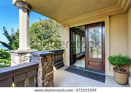 Luxury house exterior. Entrance column porch with railings and rug Open front door. Northwest, USA #473193349