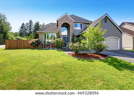 Luxury house exterior with brick and siding trim and double garage. Well kept garden around. Northwest, USA #469328096