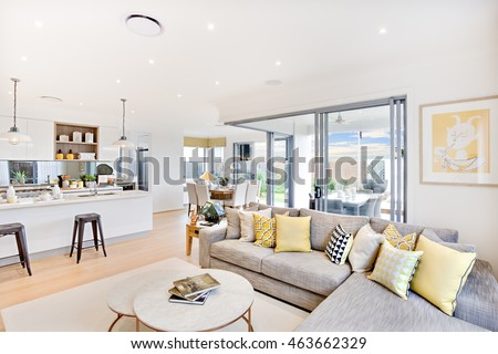 Luxury house interior focusing the living room sofa and pillows  next round table on the carpet beside the kitchen and the glass door entrance to outside #463662329