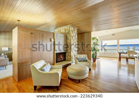 Luxury house interior. Sitting area with leather armchairs and leather ottoman. Cabinet with fireplace and rock wall trim