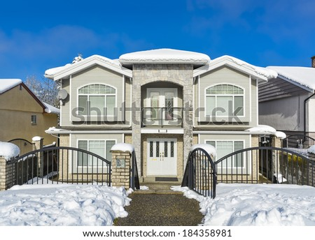 Luxury House With Metal Fence In Front And Blue Sky