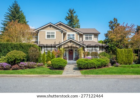 Luxury house with nicely trimmed front yard, lawn in a residential neighborhood. Home exterior.