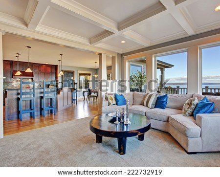 Luxury house with open floor plan. Cozy living room in light tones with comfortable sofa and coffee table