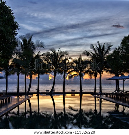Luxury infinity pool at sunset, overlooking the gulf of Thailand.