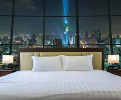 Luxury Interior bedroom with windows glass beside Top view of Bangkok Cityscape at night, Mahanakhon, relax and holiday concept, dicut each elements