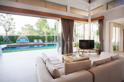 Luxury interior design in living room of pool villas. Airy and bright space with high raised ceiling, sofa, middle table  home, house , building , hotel, resort