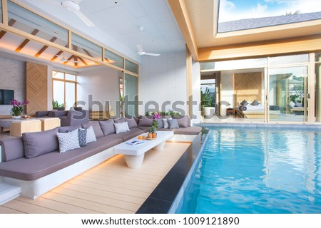 Luxury interior design in living room of pool villas. Airy and bright space with high raised ceiling and wooden dining table home, house ,sunbed ,building #1009121890