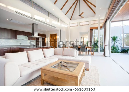 Luxury interior design in living room of pool villas. Airy and bright space with high raised ceiling, sofa, middle table, dining table and open kitchen home, house, building , resort