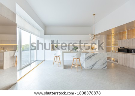 luxury interior design of modern trendy snow white kitchen in minimalistic style with island and two bar stools. huge windows to the floor and a glass rack for dishes