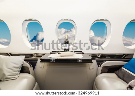 Luxury interior in bright colors of genuine leather in the business jet, sky and clouds through the porthole ストックフォト ©