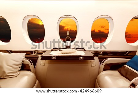 Luxury interior in bright colors of genuine leather in the business jet, sky, clouds and sunset through the porthole ストックフォト ©