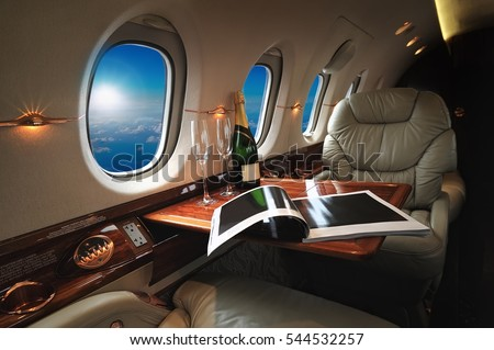 luxury interior in the modern  business jet and sunlight at the window/sky and clouds through the porthole #544532257