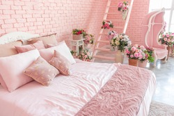 luxury interior of large bedroom in pink colors with expensive furniture in rich barocco style decorated with flowers in vases.