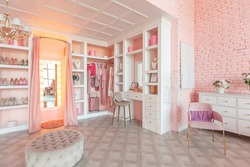 luxury interior of large room in pink colors with expensive furniture in rich barocco style decorated with flowers in vases. wardrobe-room for clothes, shoes and various personal items