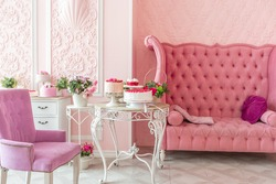 luxury interior of large room in pink colors with expensive furniture in rich barocco style decorated with flowers in vases.  openwork lace breakfast table