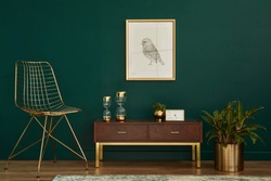 Luxury interior with stylish chair, wooden commode, mock up poster frame, plants, gold decoration and elegant personal accessories. Modern living room in classic house. Template.