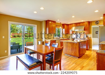 Luxury kitchen room with island, dining table set and exit to backyard patio area