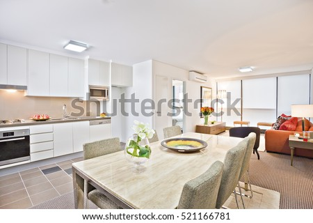 Luxury kitchen with modern table and sofa, wash basin also gas cooker have attached to the wall, flower pot near ceramic plate on  dining table, chairs are cushioned in white color.