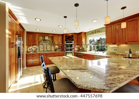 Luxury kitchen with tile floor, stained cabinets and granite counter top #447557698