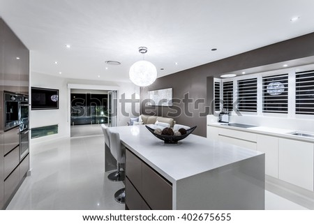 Luxury kitchen with wall oven cabinets next to the fancy items on the white counter top illuminated using round hanging lamp