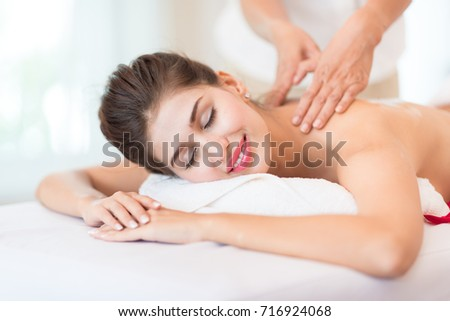 Luxury Lady Relaxing Massage Body Spa Therapy - Woman Lying with closed eyes and having a wellness back massage and feeling visibly good - Healthy Lifestyle and Relaxation Concept.