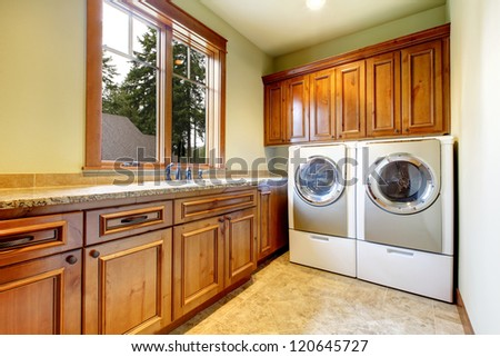 Luxury laundry room with wood cabinets and tile floor.