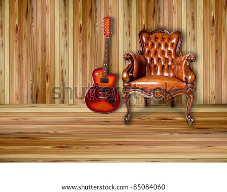 luxury leather armchair and sunburst electric guitar on wood background