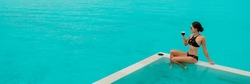 Luxury lifestyle elegant bikini woman drinking coffee cup by infinity swimming pool at overwater bungalow overlooking turquoise pristine ocean. Panoramic banner.
