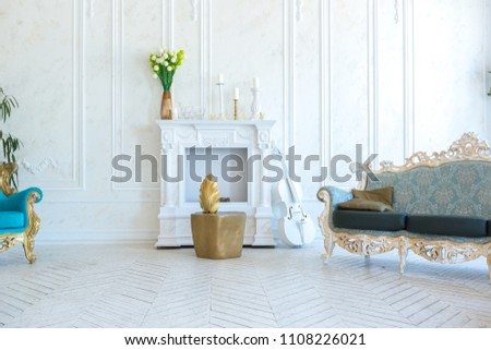 Luxury light interior of living room with gold wall and chic expensive furniture in white and gold colors #1108226021