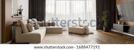 Luxury living room with big beige corner sofa and wooden floor and big windows, panorama