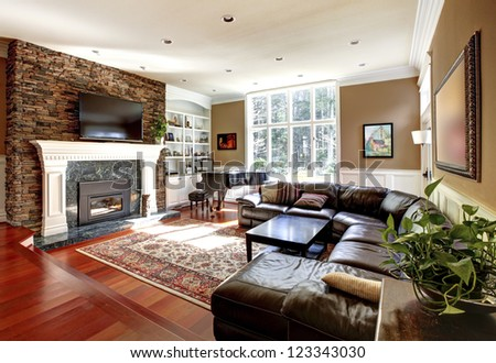 Luxury living room with stone fireplace and leather sofas, cherry hardwood and nice rug. #123343030