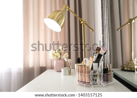 Luxury makeup products and accessories on dressing table with mirror. Space for text