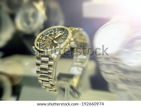 Luxury men\'s watches in the shop windows. Lens flare. Motion blur.