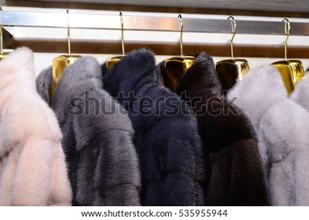 Luxury mink coats. Pink, grey, dark grey, pearl color fur coats on showcase of market. Best gift for a woman. Outerwear. Close up. #535955944